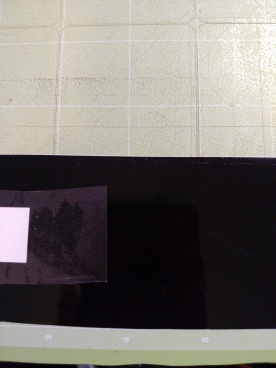 Adhesive vinyl cut, but still on the mat, with transfer tape applied.